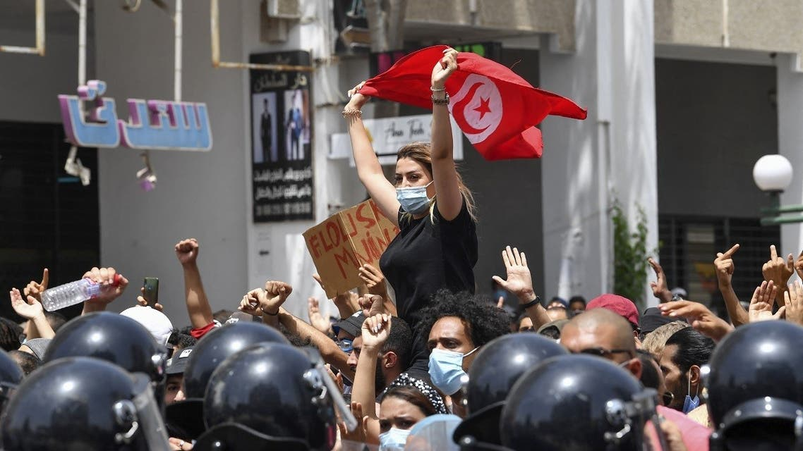 A Tunisian protester lifts a national flag at an anti-government rally as security forces block off the road in front of the Parliament in the capital Tunis on July 25, 2021. (AFP)