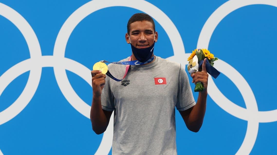 Gold medalist Ahmed Hafnaoui of Tunisia poses on the podium. (Reuters)