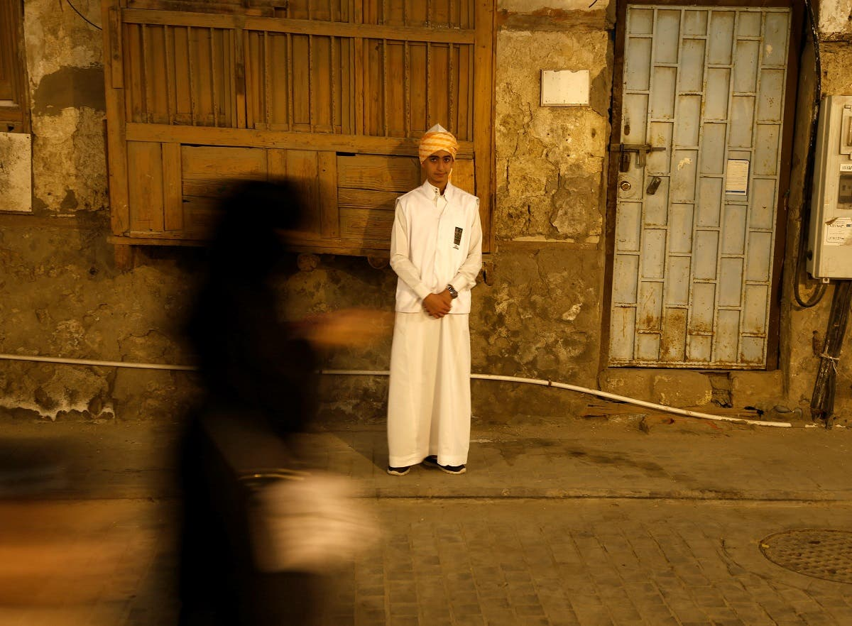 Woman walks past a boy wearing traditional costumes during the holy fasting month of Ramadan at Jeddah's historical area Al-Balad. (Reuters)