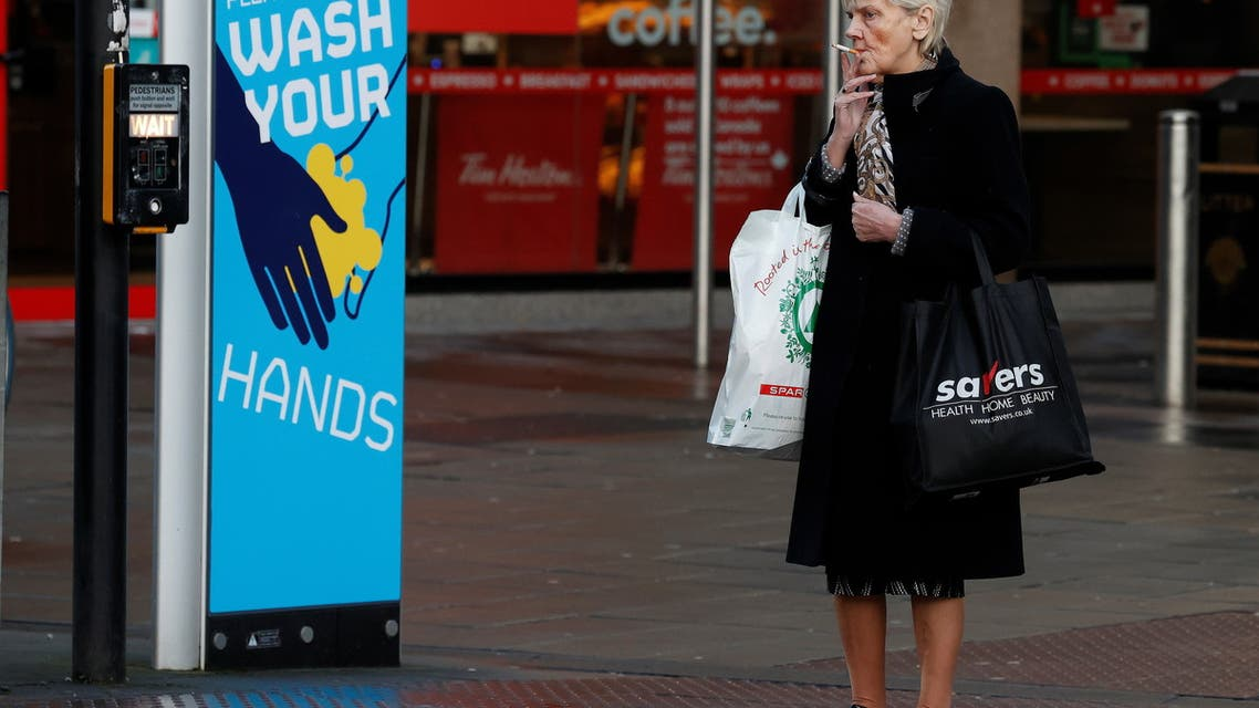 A woman smokes a cigarette as she stands by a sign encouraging people to wash their hands amid the outbreak of the coronavirus disease (COVID-19) in Belfast, Northern Ireland January 2, 2021. (Reuters)