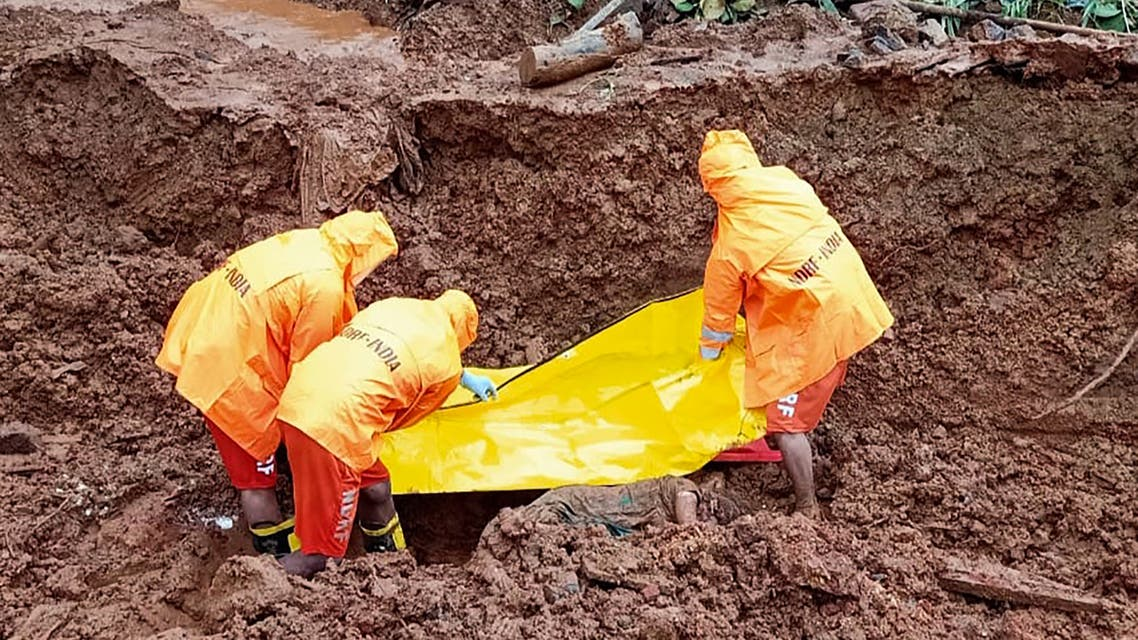 This handout photo taken on July 25, 2021 and released by India's National Disaster Response Force (NDRF), shows NDRF personnel recovering the body of a victim at the site of a landslide after heavy monsoon rains at Posare Khurd village in Khed district of Maharashtra. (AFP)