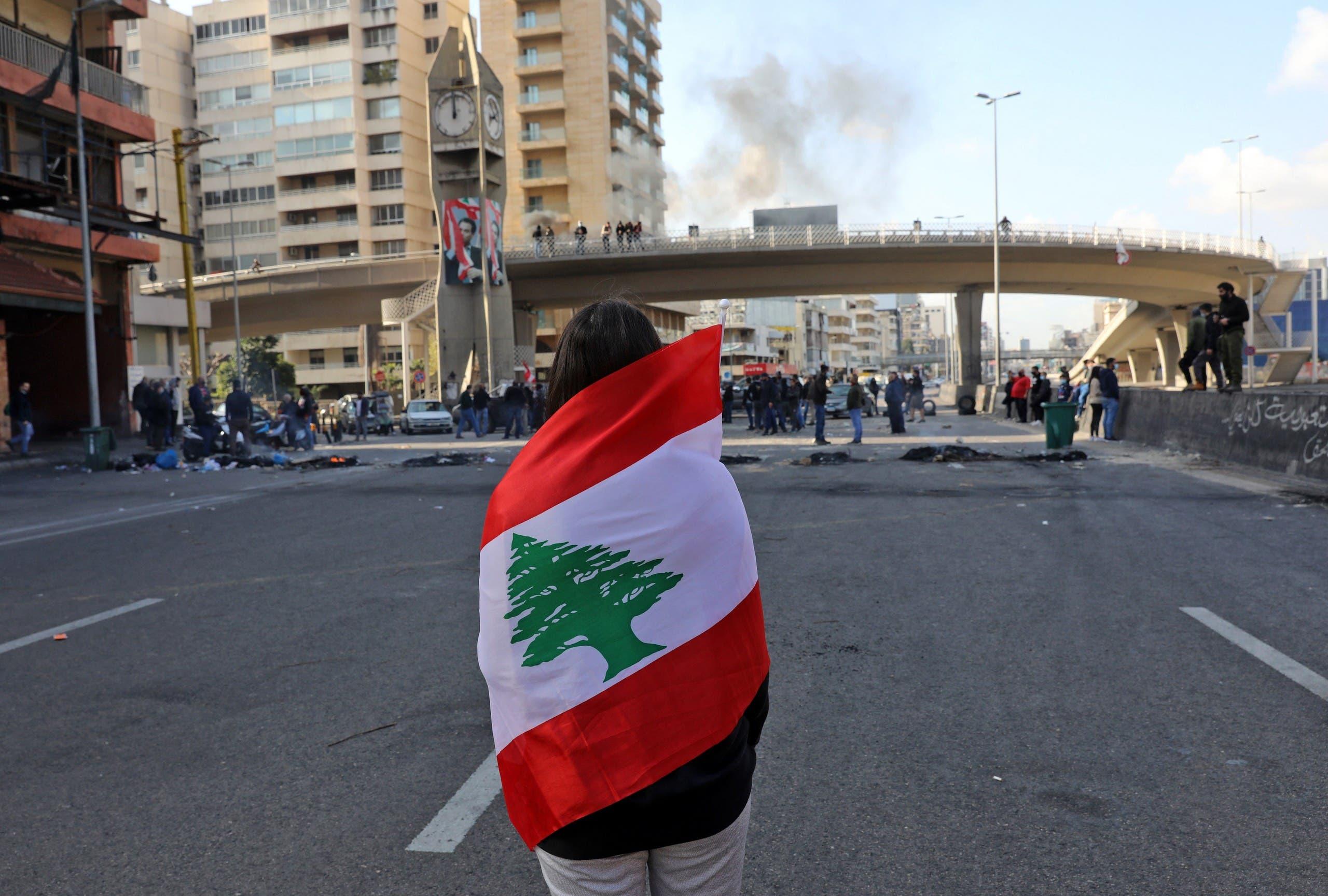 شابة ترفع العلم اللبناني في احتجاج في مارس الماضي على الأزمة التي يعيشها البلد