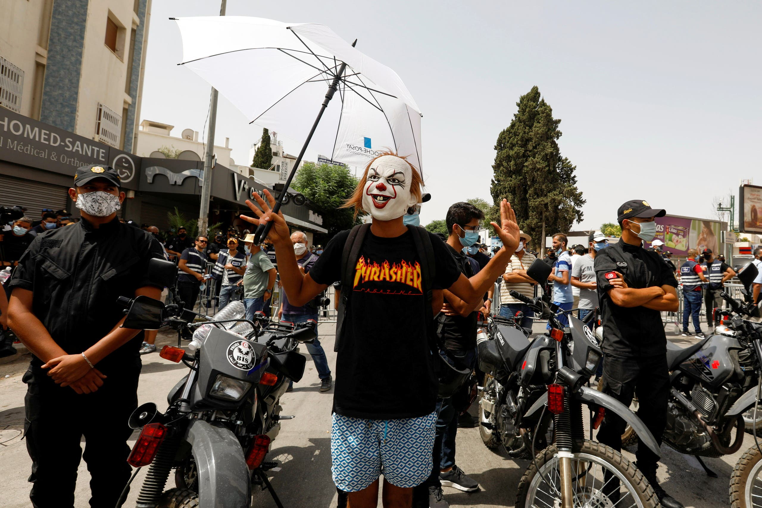 A demonstrator holding a sunshade gestures as he stands next to police officers during an anti-government protest in Tunis, Tunisia, July 25, 2021. (Reuters)