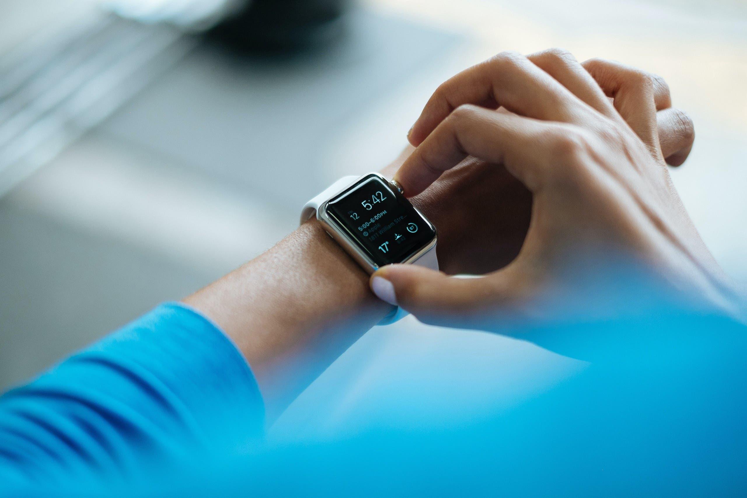 A man wearing a wearable watch to track fitness. (Unsplash, Luke Chesser)