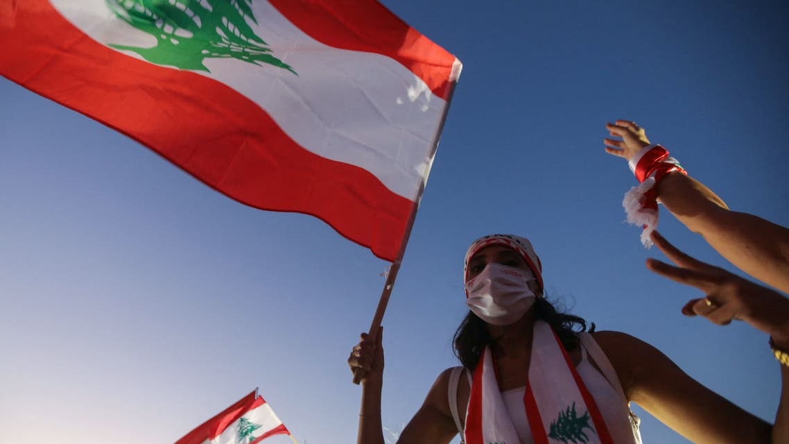 A Lebanese protester lifts a national flag during a demonstration marking the one year anniversary of the beginning of a nationwide anti-government protest movement, in the capital Beirut on October 17, 2020. Hundreds marched in Lebanon's capital to mark the first anniversary of a non-sectarian protest movement that has rocked the political elite but has yet to achieve its goal of sweeping reform.