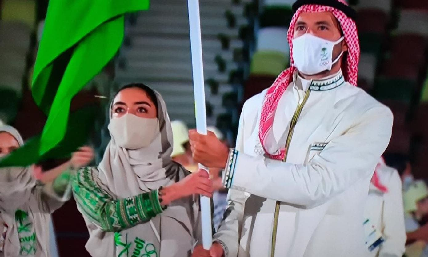 Yasmeen al-Dabbagh and Hussein Ali Reda carry the Saudi Arabian flag at the opening of the Tokyo Olympics. (Twitter)