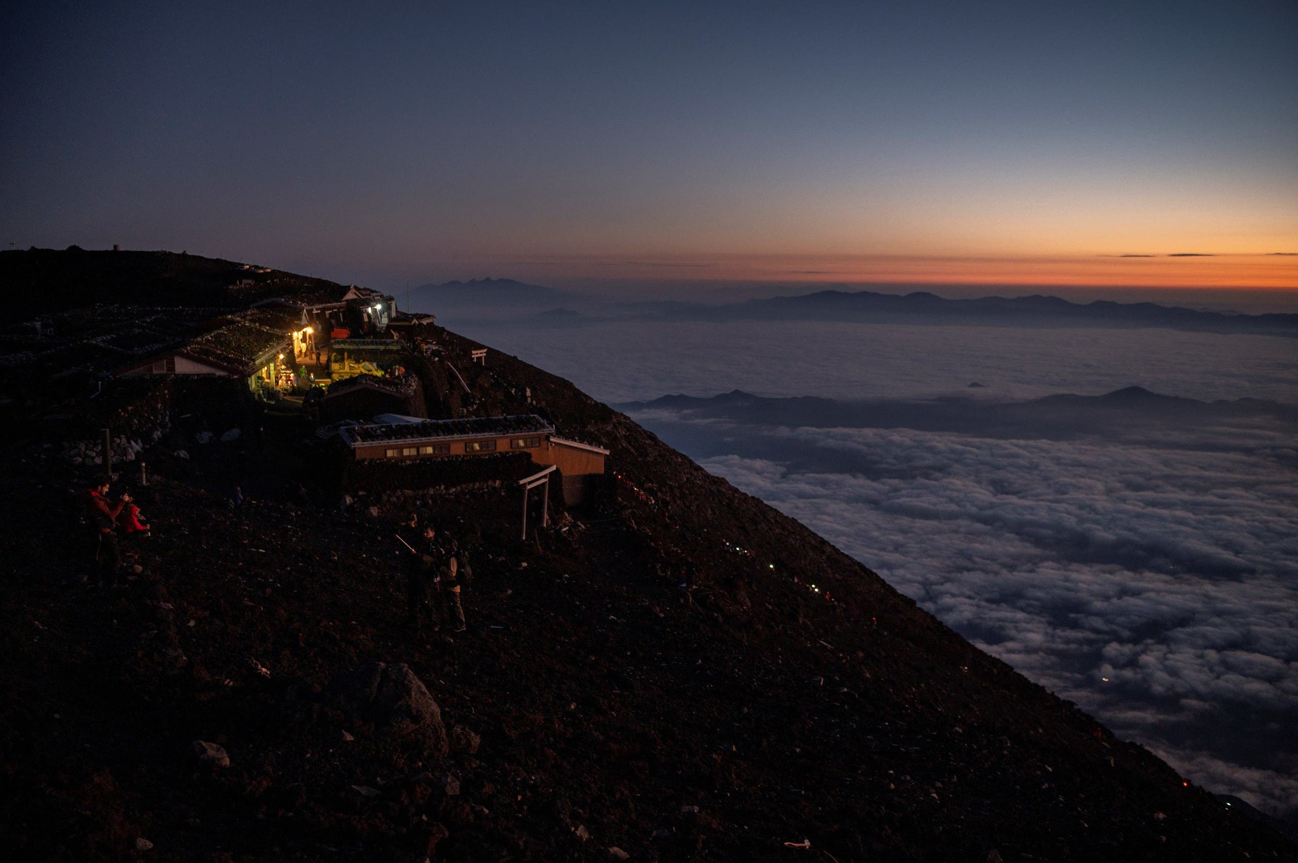 This photo taken on July 19, 2021 shows a line of lights (C) as people make their way up the trail to watch the sunrise from the summit of Mount Fuji, some 70 kilometres (43 miles) west of the capital Tokyo. (AFP)