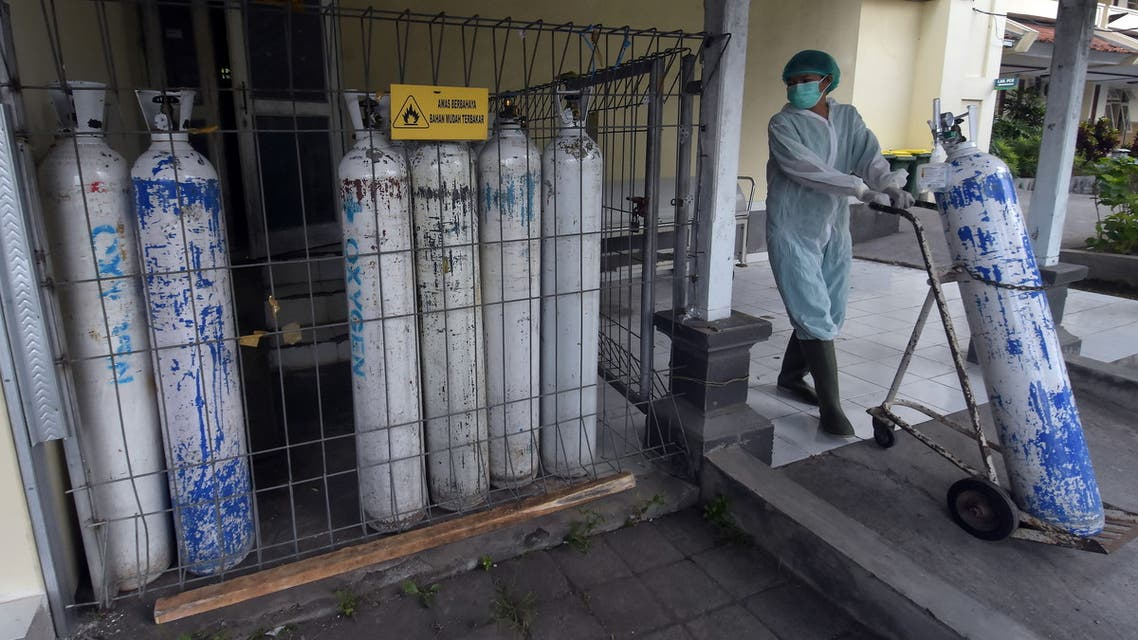 A medical worker pulls an oxygen cylinder to be delivered to the emergency ward at a government-run hospital amid the coronavirus disease (COVID-19) outbreak in Denpasar, Bali, Indonesia, July 23, 2021, in this photo taken by Antara Foto July 23, 2021. (Reuters)