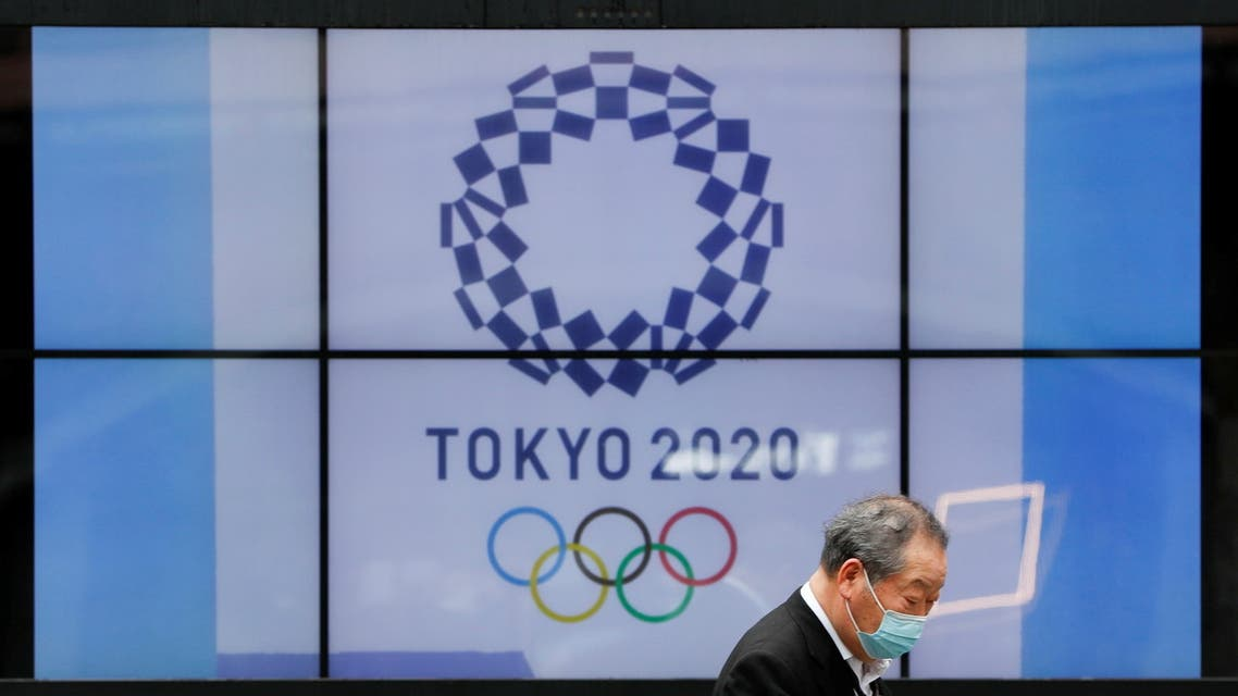 A passerby wearing a protective face mask walks past a screen showing the logo of the 2020 Olympic Games in Tokyo, Japan, April 14, 2021. (Reuters)