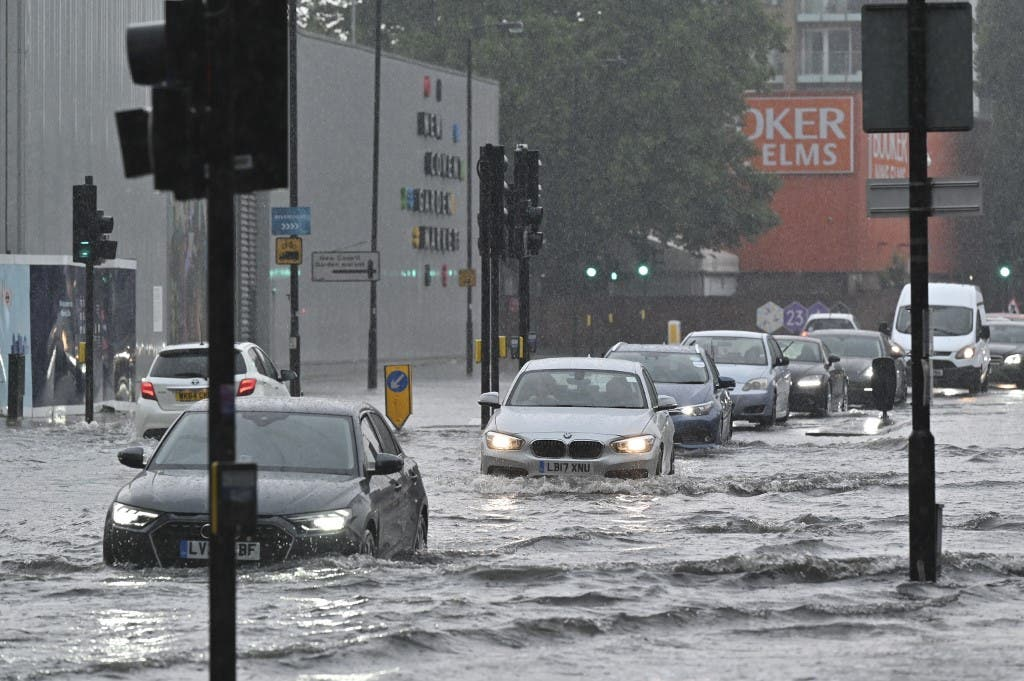 Cars drive through deep water on a flooded road in The Nine Elms district of London on July 25, 2021 during heavy rain. Buses and cars were left stranded when roads across London flooded on Sunday, as repeated thunderstorms battered the British capital. (AFP)