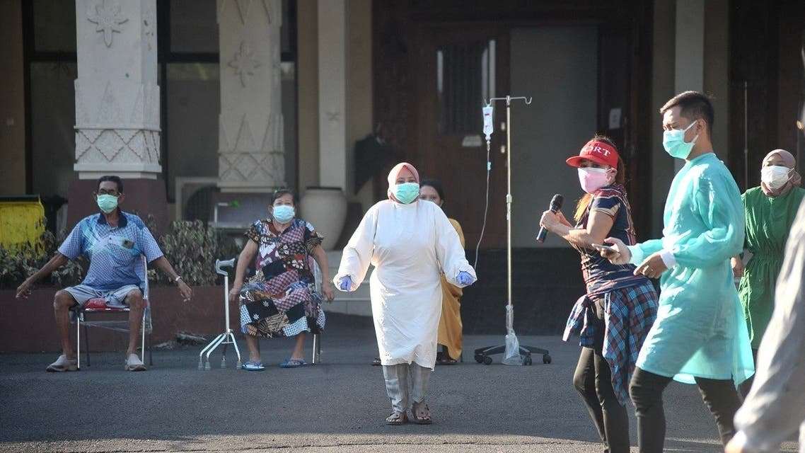 Medical workers lead a group of recovering Covid-19 patients in a group exercise outside a hospital in Semarang on July 25, 2021. (AFP)
