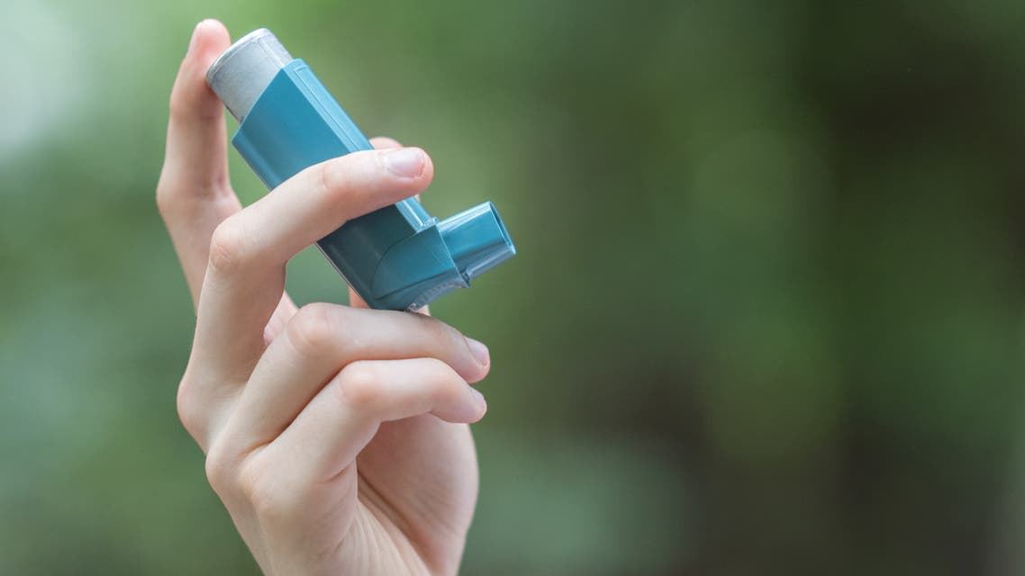 A picture of a man's hand holding a blue inhaler. (iStock)