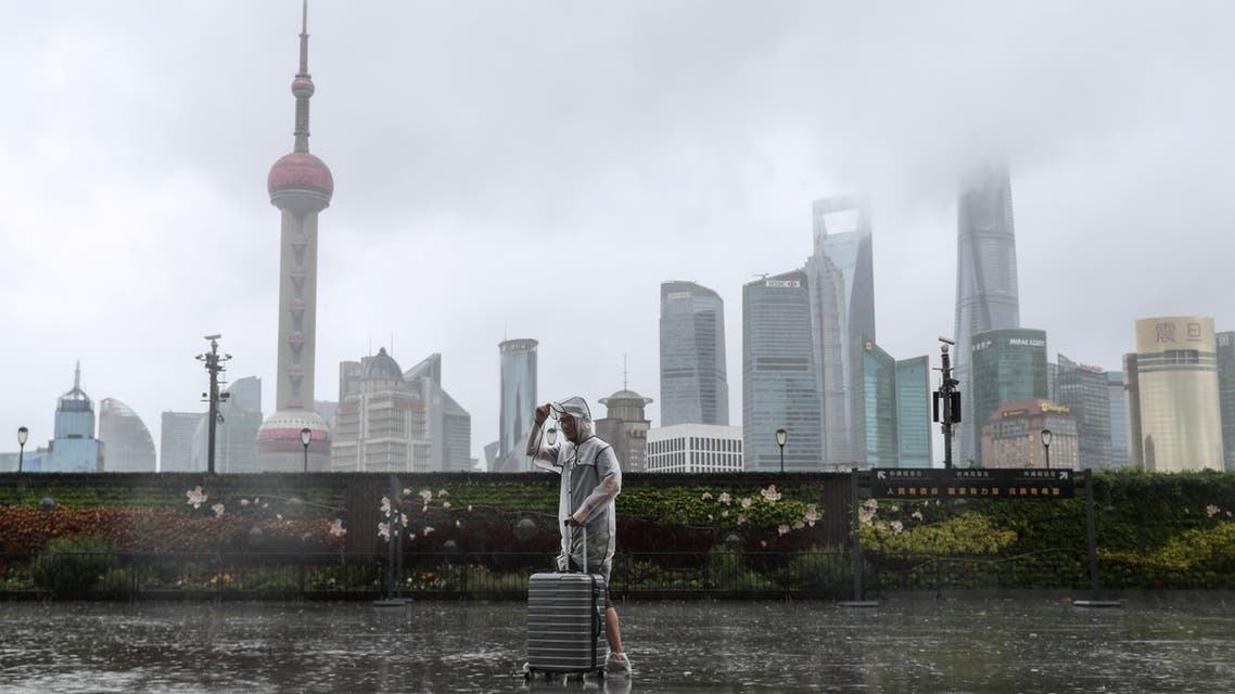 A man with luggage walks in the rain on The Bund as Typhoon In-fa approaches Shanghai, China July 25, 2021. cnsphoto via REUTERS ATTENTION EDITORS - THIS IMAGE WAS PROVIDED BY A THIRD PARTY. CHINA OUT.