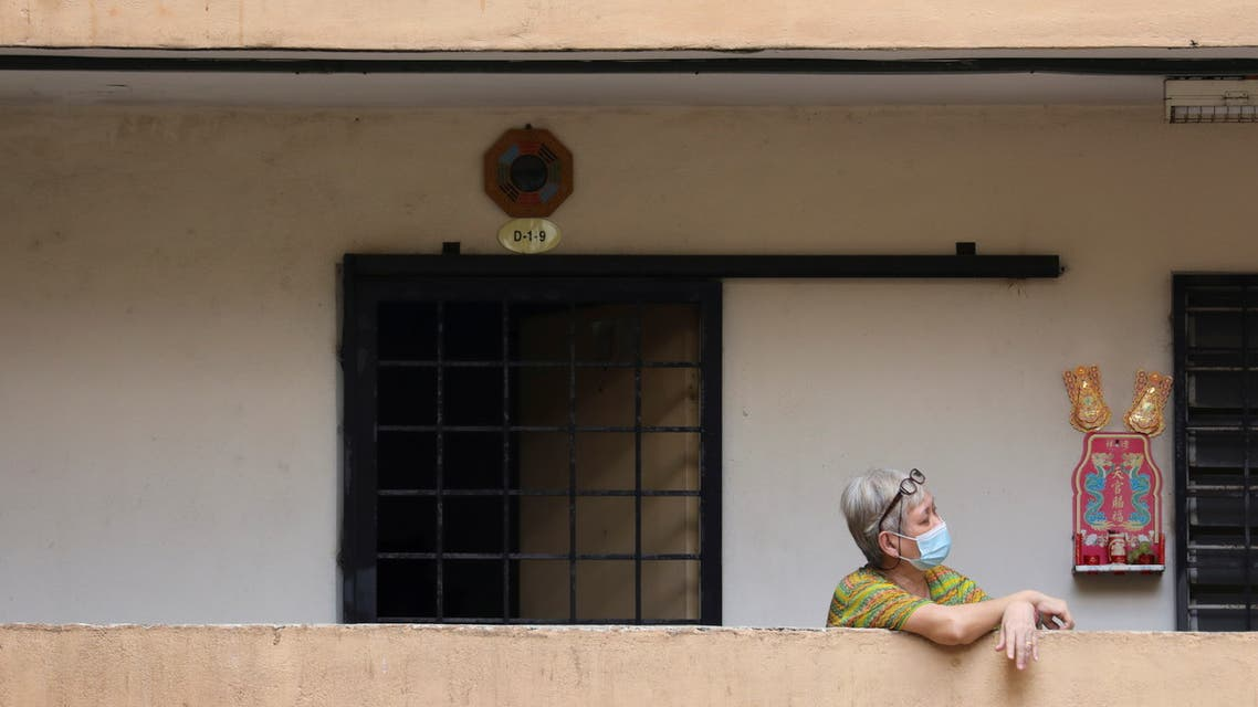 A woman wearing a protective face mask rests outside her home during an enhanced lockdown, amid the coronavirus disease (COVID-19) outbreak, in Kuala Lumpur, Malaysia July 3, 2021. (Reuters)