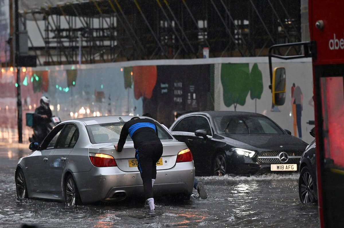 A person pushes a broken-down car through deep water on a flooded road in The Nine Elms district of London on July 25, 2021 during heavy rain. Buses and cars were left stranded when roads across London flooded on Sunday, as repeated thunderstorms battered the British capital. (AFP)