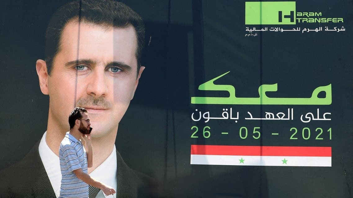 A man talks on his mobile phone as he walks past an election campaign billboard depicting Syrian President Bashar al-Assad, a candidate for the upcoming presidential vote, in the capital Damascus on May 23, 2021. (AFP)