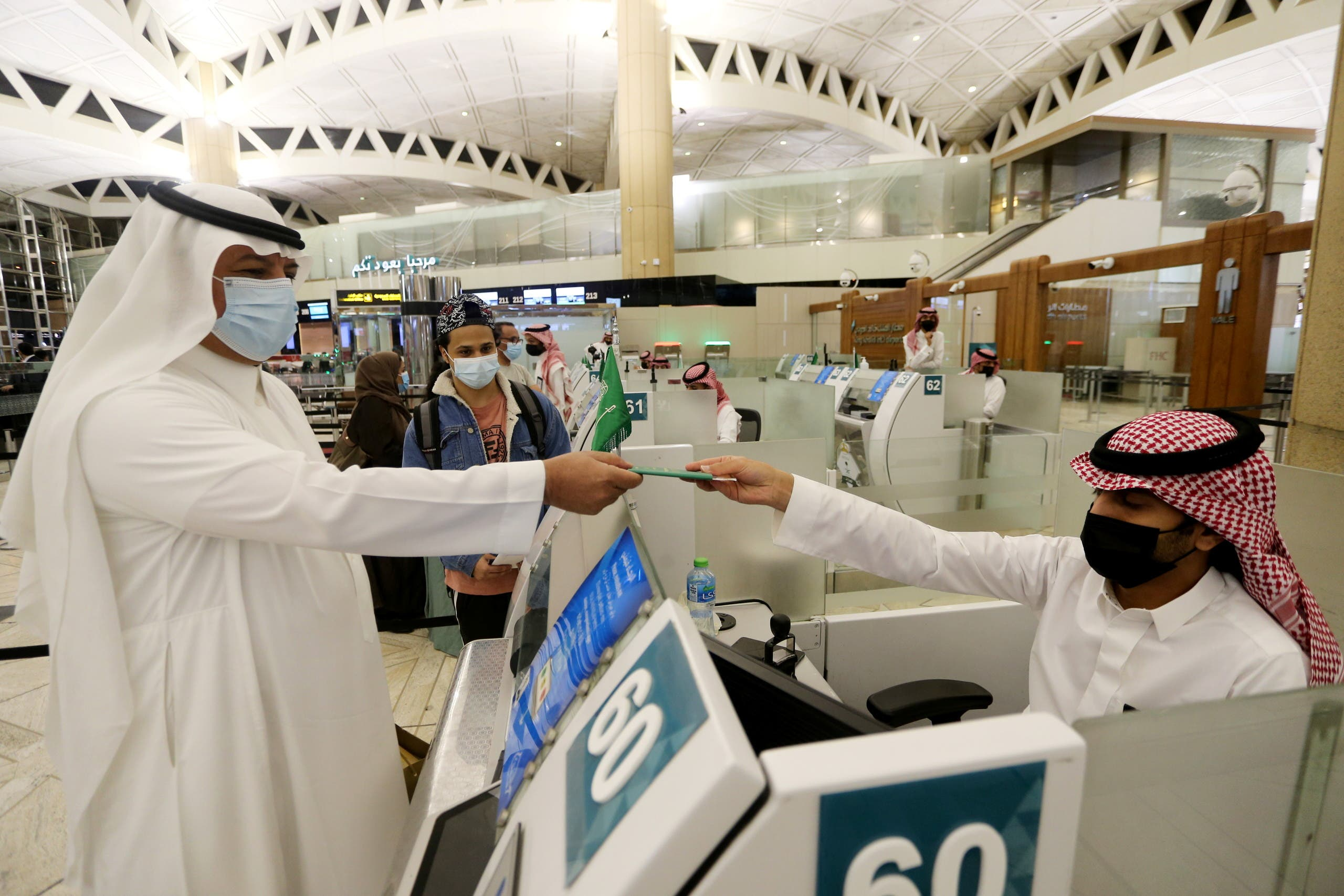 A Saudi man wearing a face mask gets his passport from a Saudi Immigration officer, at the King Khalid International Airport, after Saudi authorities lifted the travel ban on its citizens after fourteen months due to coronavirus disease (COVID-19) restrictions, in Riyadh, Saudi Arabia, May 16, 2021. (Reuters)