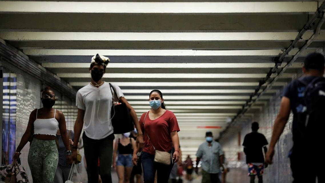 People wear masks as they pass through a pedestrian subway as cases of the infectious coronavirus Delta variant continue to rise in New York City, New York, US, on July 26, 2021. (Reuters)