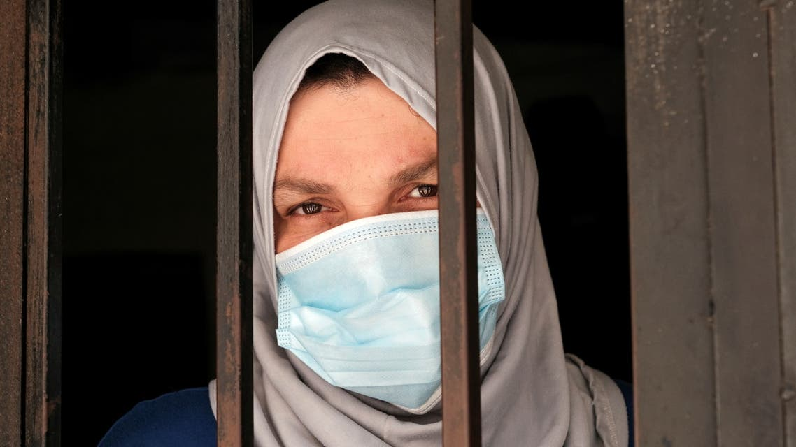 A woman looks through a window in Tripoli, Lebanon June 21, 2021. Picture taken June 21, 2021. REUTERS/Emilie Madi