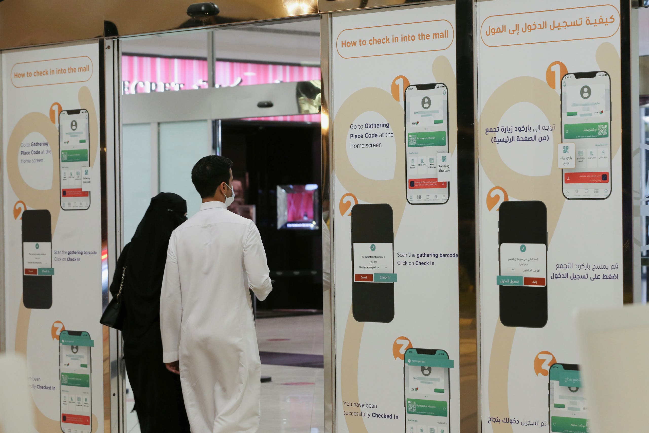 A Saudi man and his wife enter Granada Mall, after displaying the Tawakolna app, launched by the Saudi authorities to help track people infected with the coronavirus disease (COVID-19), in Riyadh, Saudi Arabia March 3, 2021. (Reuters)
