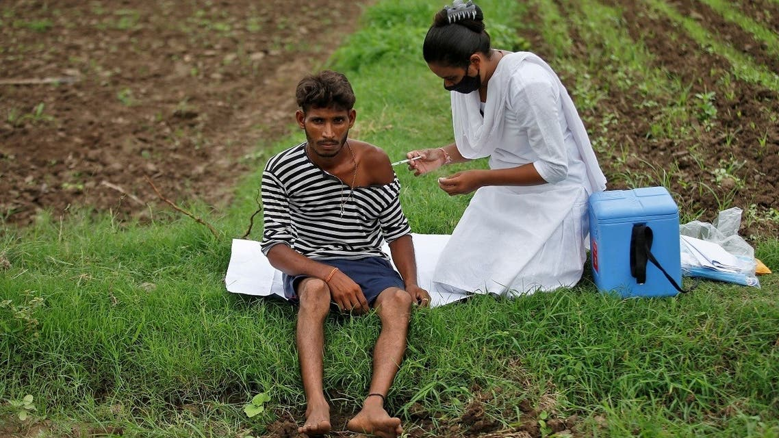 Healthcare worker Jankhana Prajapati gives a dose of the COVISHIELD vaccine against the coronavirus , manufactured by Serum Institute of India, to farmer Nareshbhai Dabhi in his field, during a door-to-door vaccination drive in Banaskantha district in the western state of Gujarat, India, on July 23, 2021. (Reuters)