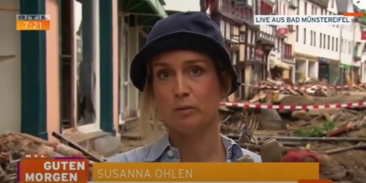 Reporter Susanna Ohlen from German channel RTL smears mud onto herself in an attempt to pretend to clear up flood-ravaged areas in Germany. (Screengrab via YouTube)