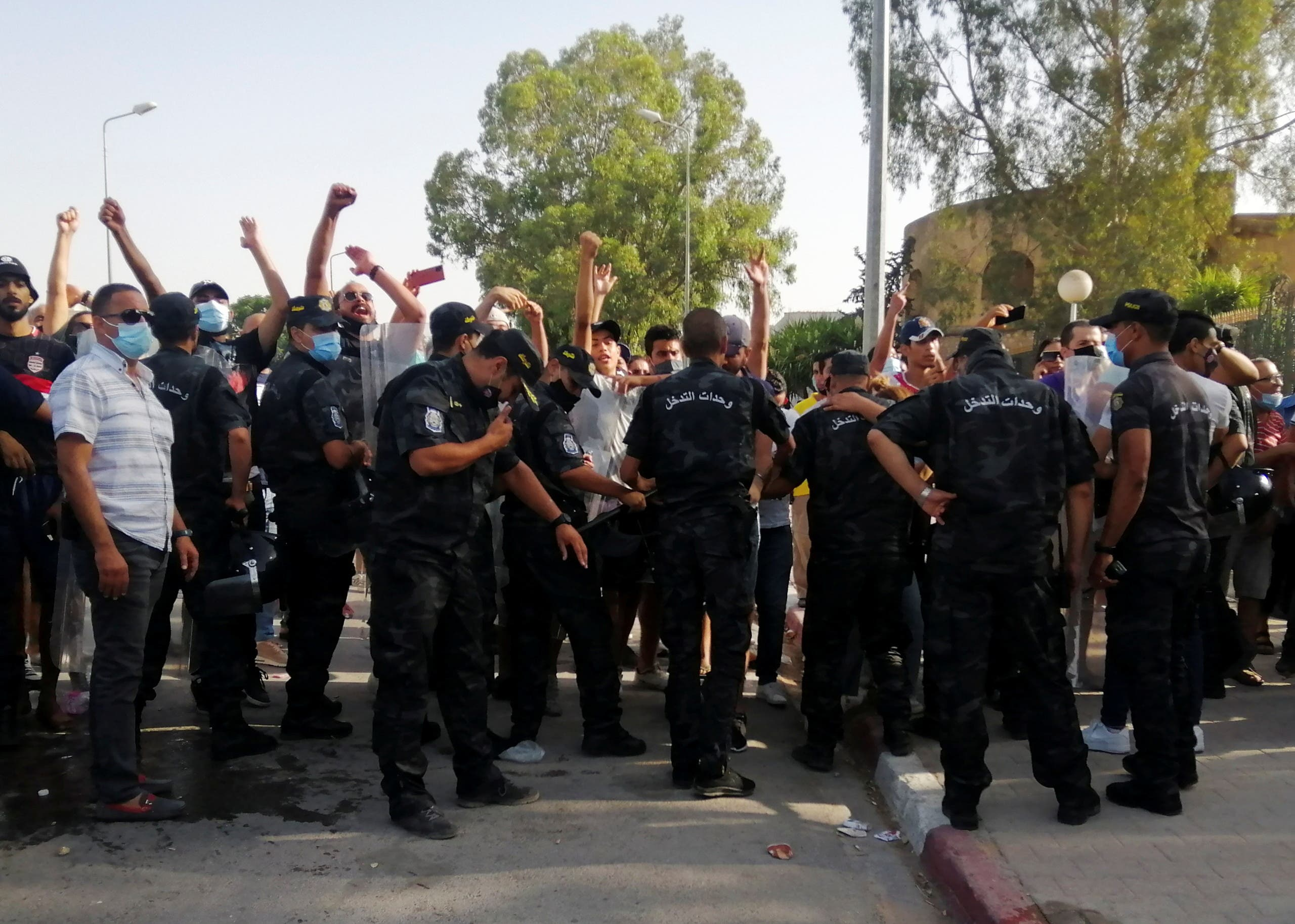 Police officers stand guard as supporters of Tunisia's biggest political party, the moderate Islamist Ennahda, gather outside the parliament building in Tunis, Tunisia July 26, 2021. (Reuters)
