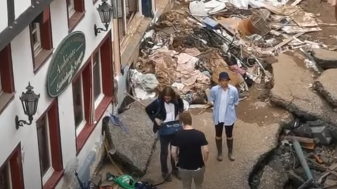 German reporter smears mud on clothes, pretends to clear up flood-ravaged town2. (Screengrab via YouTube)