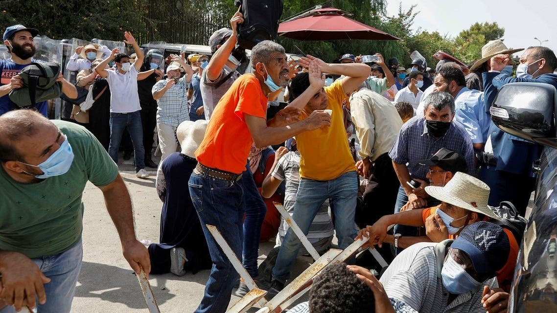 Supporters of Tunisia's biggest political party, the moderate Islamist Ennahda, take cover from stones thrown at them by supporters of President Kais Saied, outside the parliament building in Tunis, July 26, 2021. (Reuters)