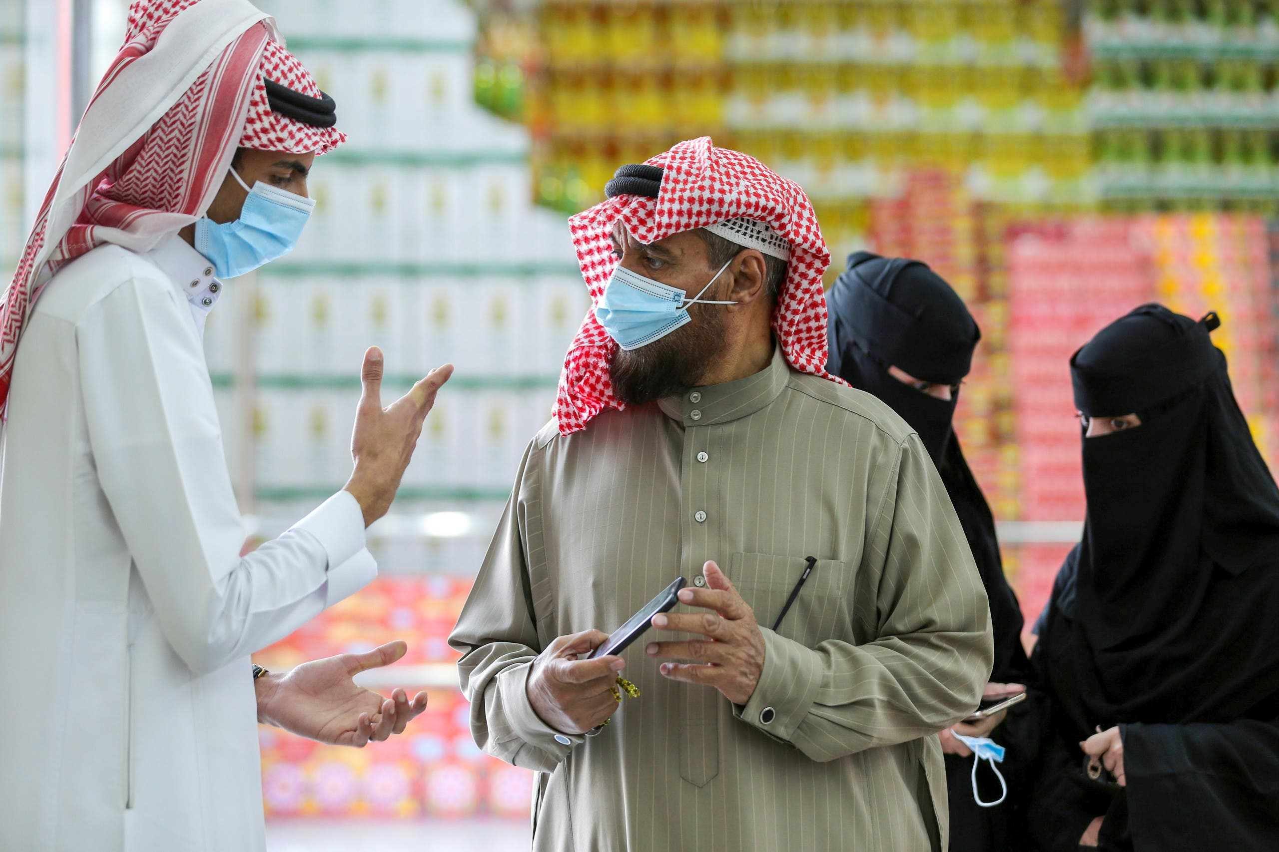 A man displays his details on his mobile phone using the Tawakkalna app, which was launched by Saudi authorities to track people infected with the coronavirus disease (COVID-19), as he enters the Al-Othaim market in Riyadh, Saudi Arabia February 22, 2021. (Reuters)