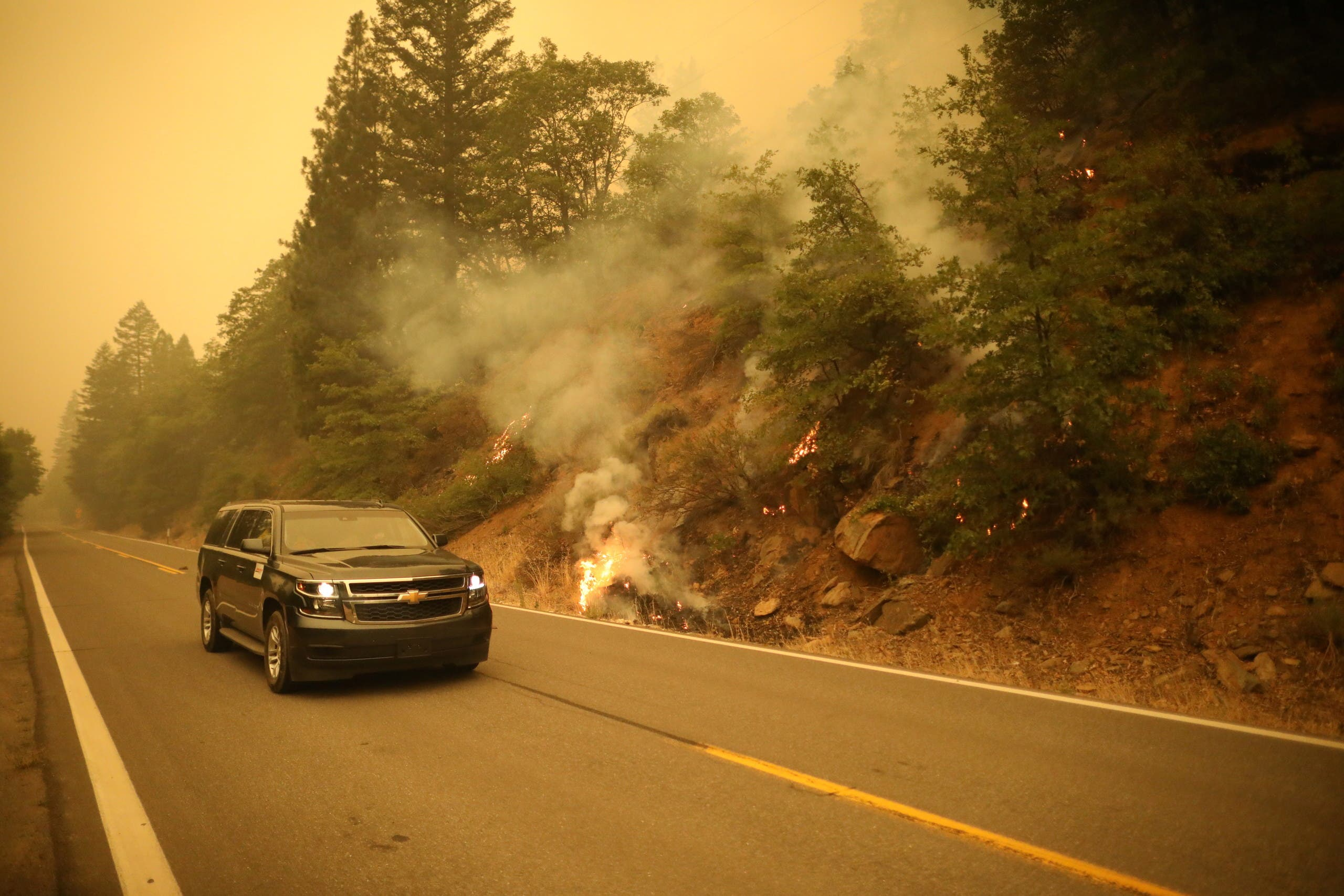 A car rides next to burning bushes as the Dixie Fire continues in Indian Falls, California, US, July 26, 2021. (Reuters)