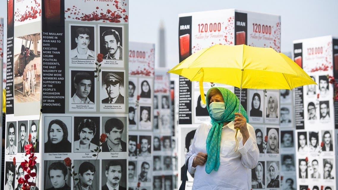 In this file photo taken on September 04, 2020 a woman with an umbrella walks past some of the thousands of photos of people killed in Iran during the 1988 massacre of political prisoners as well as during more recent anti-regime uprisings, during a photo exhibit by the Organization of the Iranian American Communities near the US Capitol in Washington, DC. (Saul Loeb/AFP)