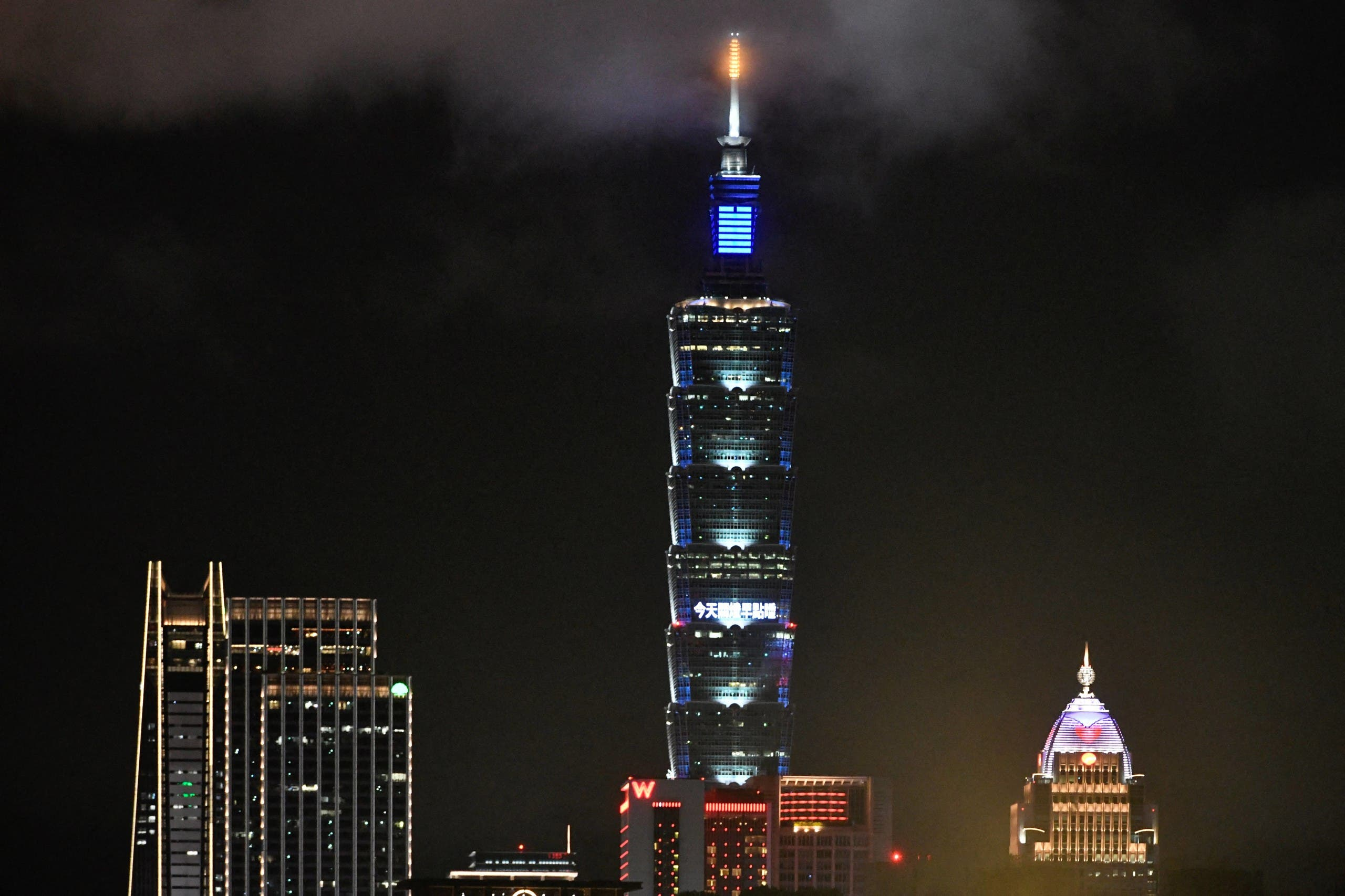 """A general view shows Taipei 101, a 508-meter high's commercial building, displays """" a turn off the light, go to sleep earlier today"""" in Chinese to mark Earth Hour Day on it's building on March 28, 2020. (AFP)"""