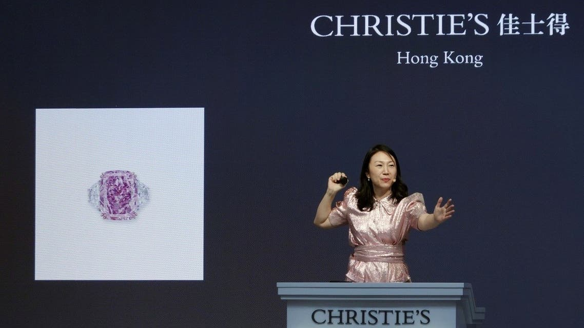 An auctioneer holds the gavel during Christie's auction of Sakura Diamond, a 15.81 carat purple pink diamond ring, in Hong Kong, China, on May 23, 2021. (Reuters)