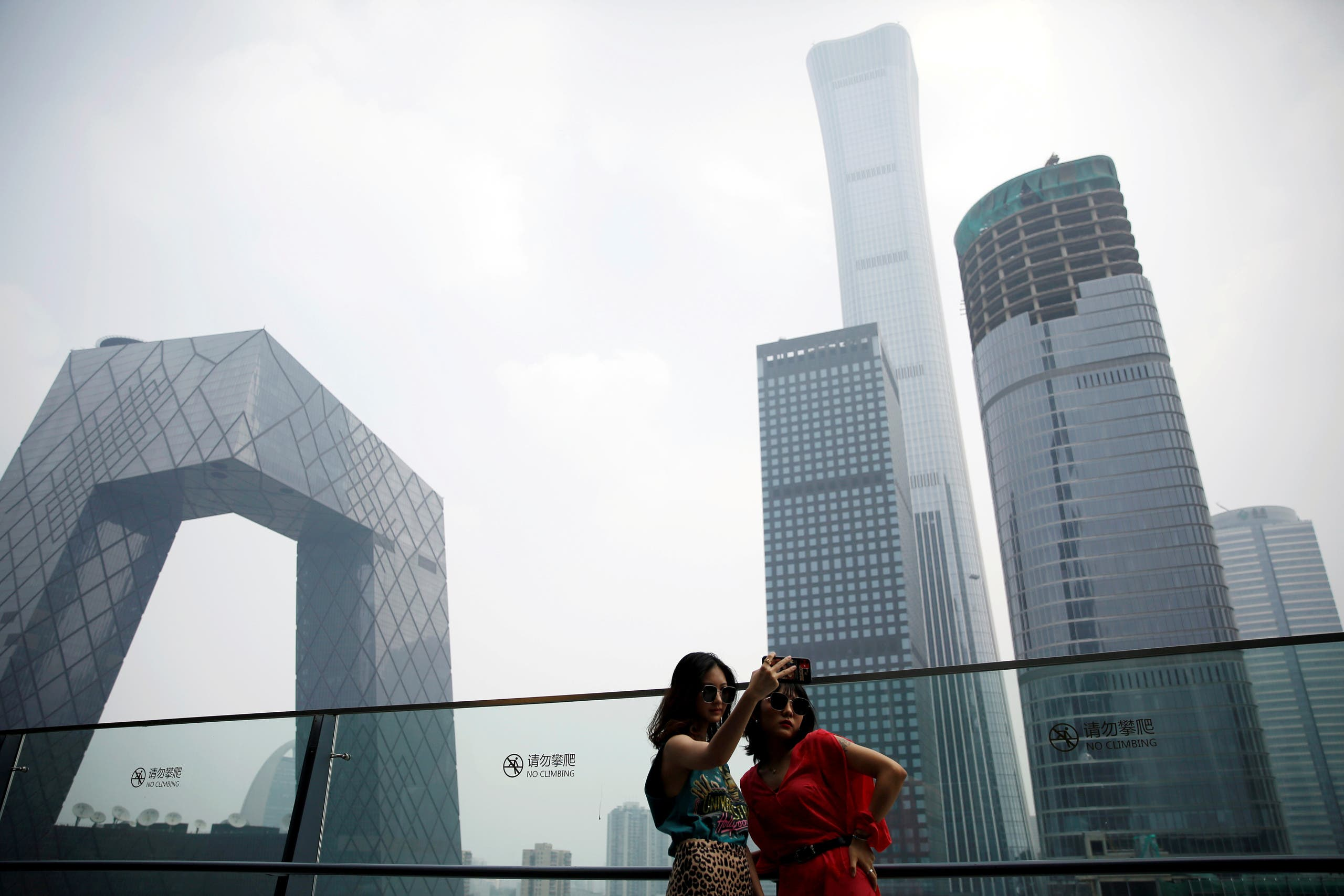 Women pose for pictures at a shopping mall near the CCTV headquarters and China Zun skyscraper in Beijing's central business district (CBD), China, July 16, 2020. (Reuters)