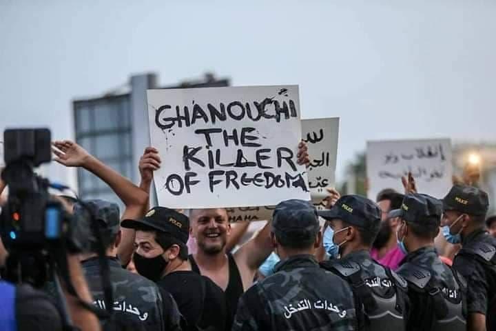 من مظاهرات أمام البرلمان التونسي وشاب يحمل لافتة كتب عليها الغنوشي قاتل الحرية