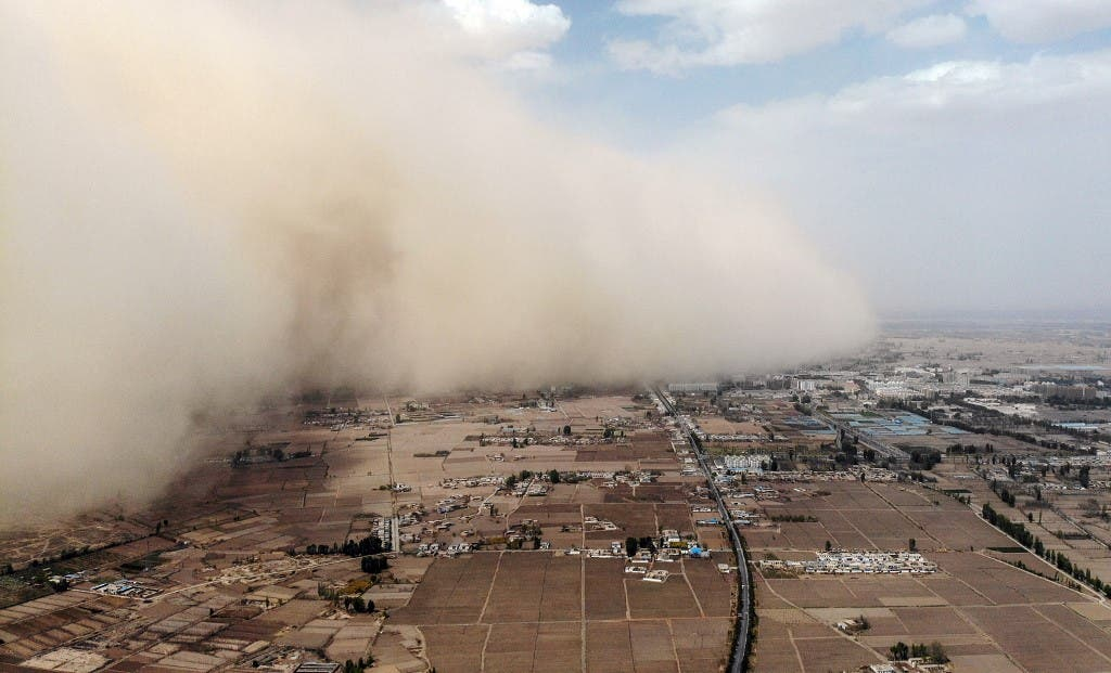 This aerial photo taken on April 25, 2021 shows a sandstorm engulfing a village in Linze county, in the city of Zhangye in China's northwestern Gansu province. (AFP)