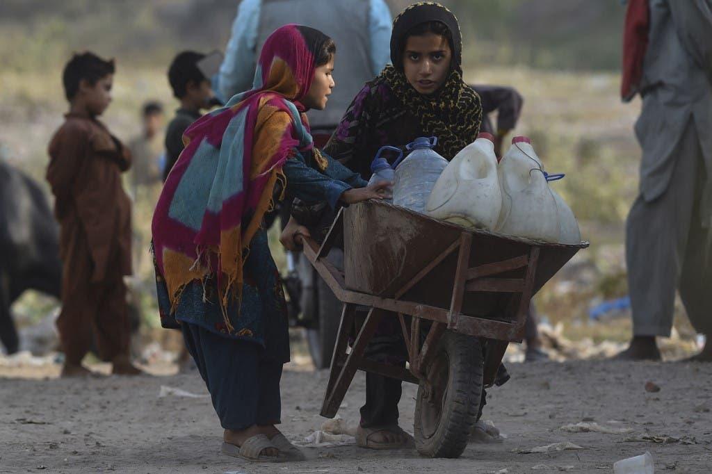 فتيات أفغانيات لاجئات يسحبن عربة محملة بزجاجات المياه في منطقة باستي الأفغانية على مشارف لاهور