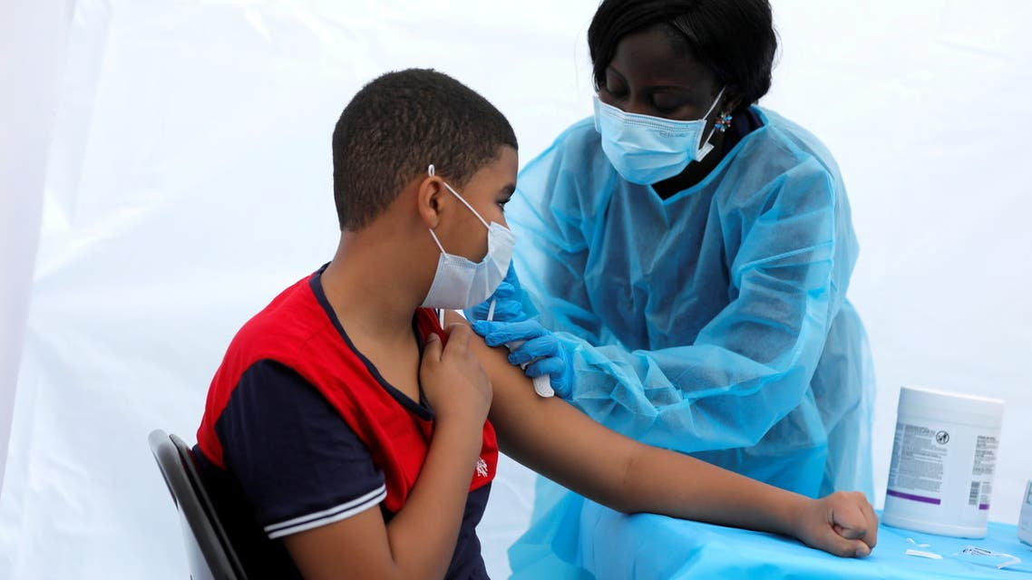 12-year-old Justing Concepcion receives a dose of the Pfizer-BioNTech vaccine for the coronavirus disease (COVID-19) from registered nurse Angela Nyarko, during a vaccination event for local adolescents and adults outside the Bronx Writing Academy school in the Bronx borough of New York City, New York, US, June 4, 2021. (File Photo: Reuters)