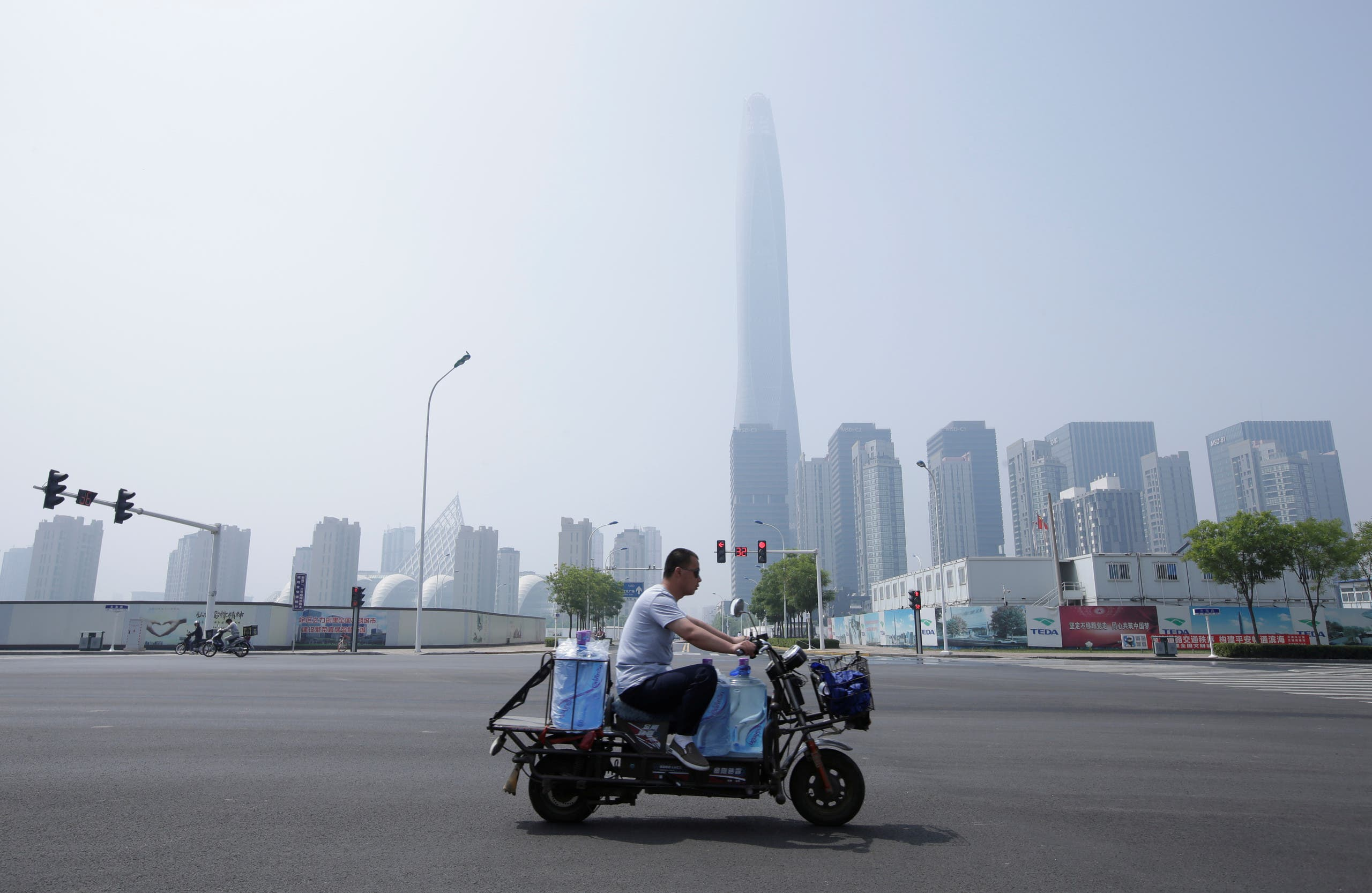 A man rides an electric motorcycle carrying water past Chow Tai Fook Financial Center in Tianjin's Binhai new district, China May 16, 2019. Picture taken May 16, 2019. (Reuters)