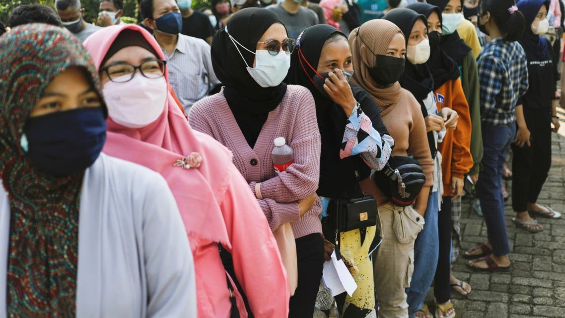 People wearing protective face masks queue to receive a dose of China's Sinovac Biotech vaccine for coronavirus disease (COVID-19) during a mass vaccination program at a school building in Jakarta, Indonesia, July 26, 2021. (Reuters)