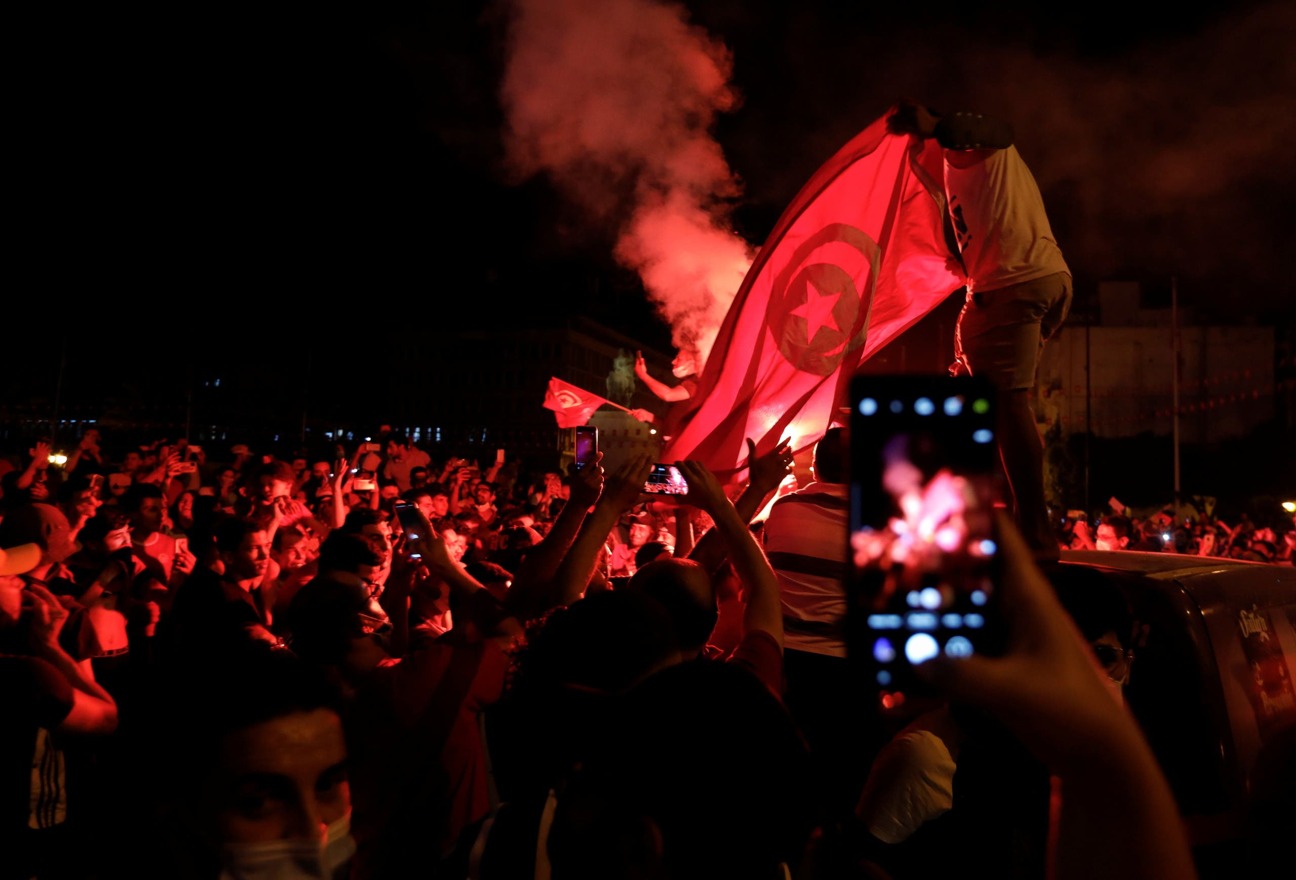 Supporters of Tunisia's President Kais Saied gather on the streets as they celebrate after he dismissed the government and froze parliament, in Tunis, Tunisia July 25, 2021. (Reuters)