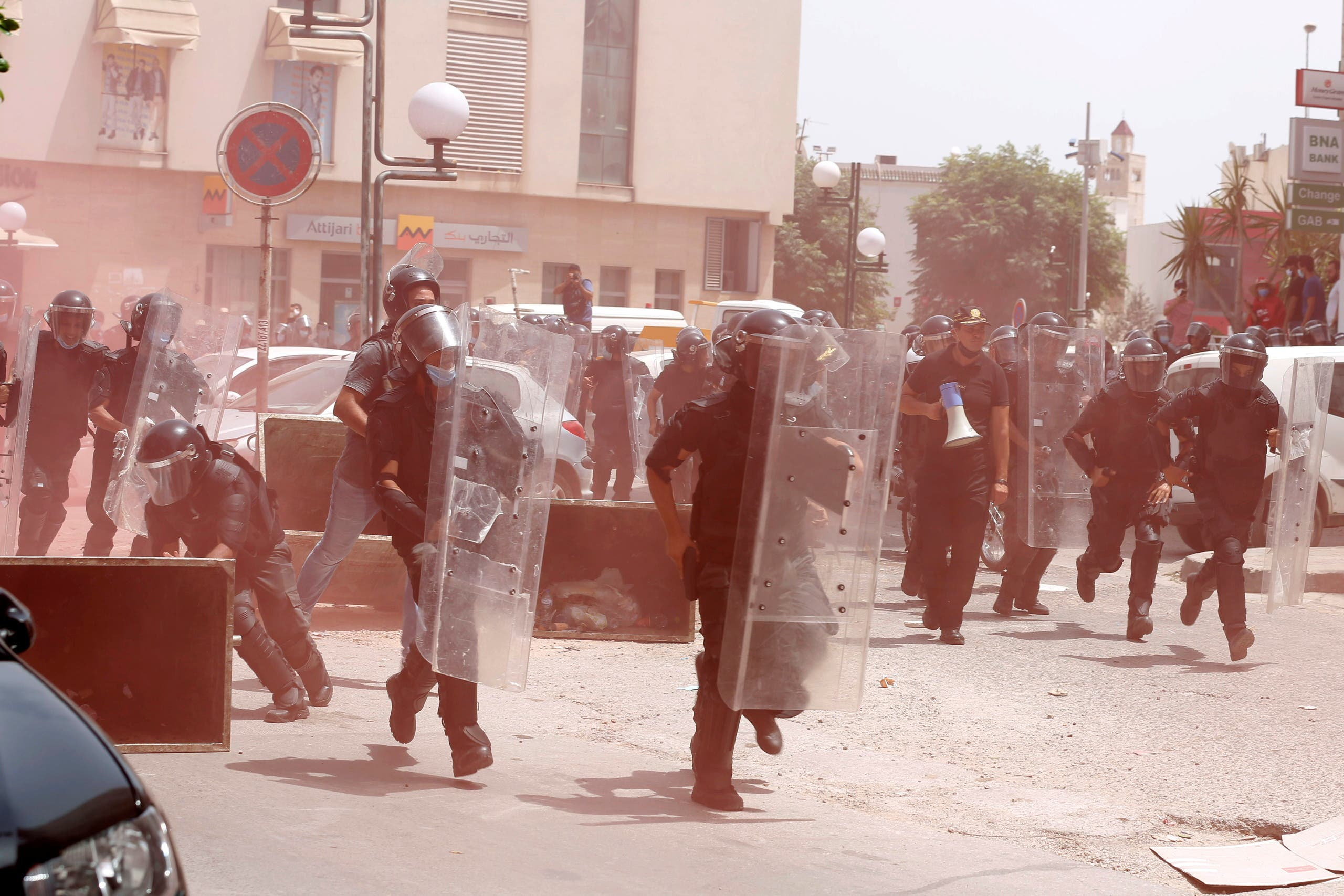Police officers run towards demonstrators during an anti-government protest in Tunis, Tunisia, July 25, 2021. (Reuters)