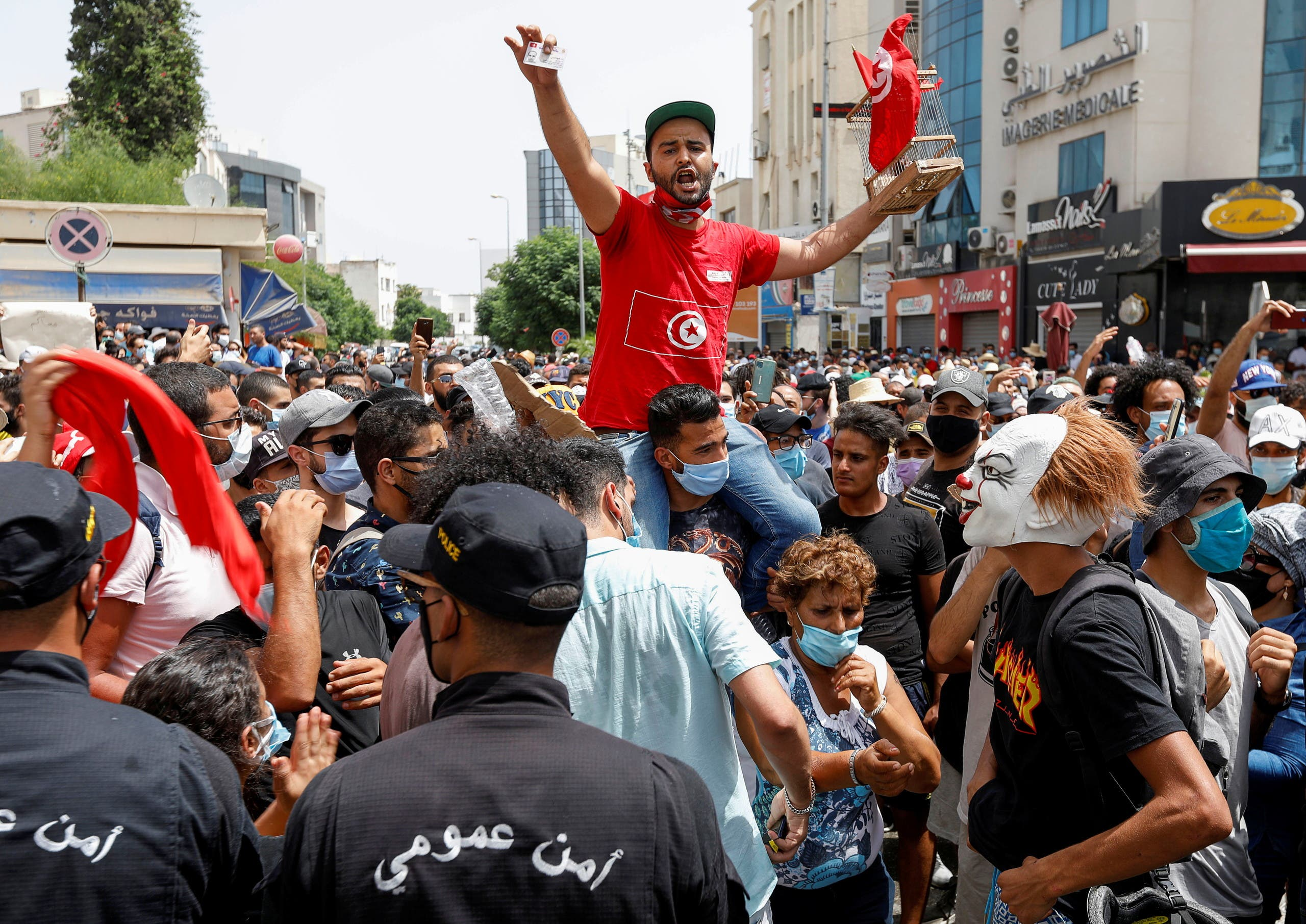 Demonstrators gather in front of police officers standing guard during an anti-government protest in Tunis, Tunisia, July 25, 2021. (Reuters)