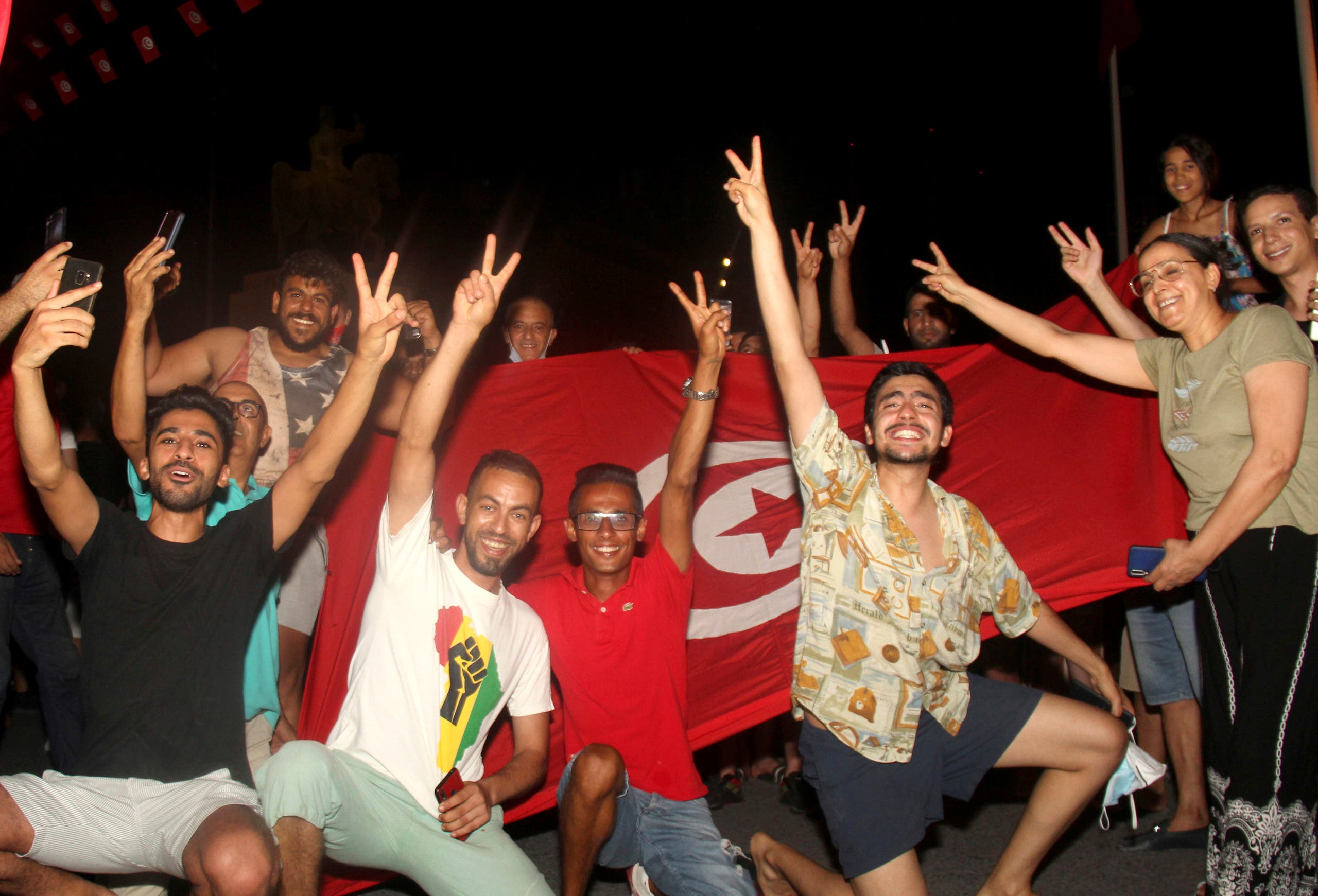 Demonstrators celebrate with a Tunisian national flag during a rally after the president suspended the legislature and fired the prime minister in Tunis, Tunisia, Sunday, July 25, 2021. (AP)