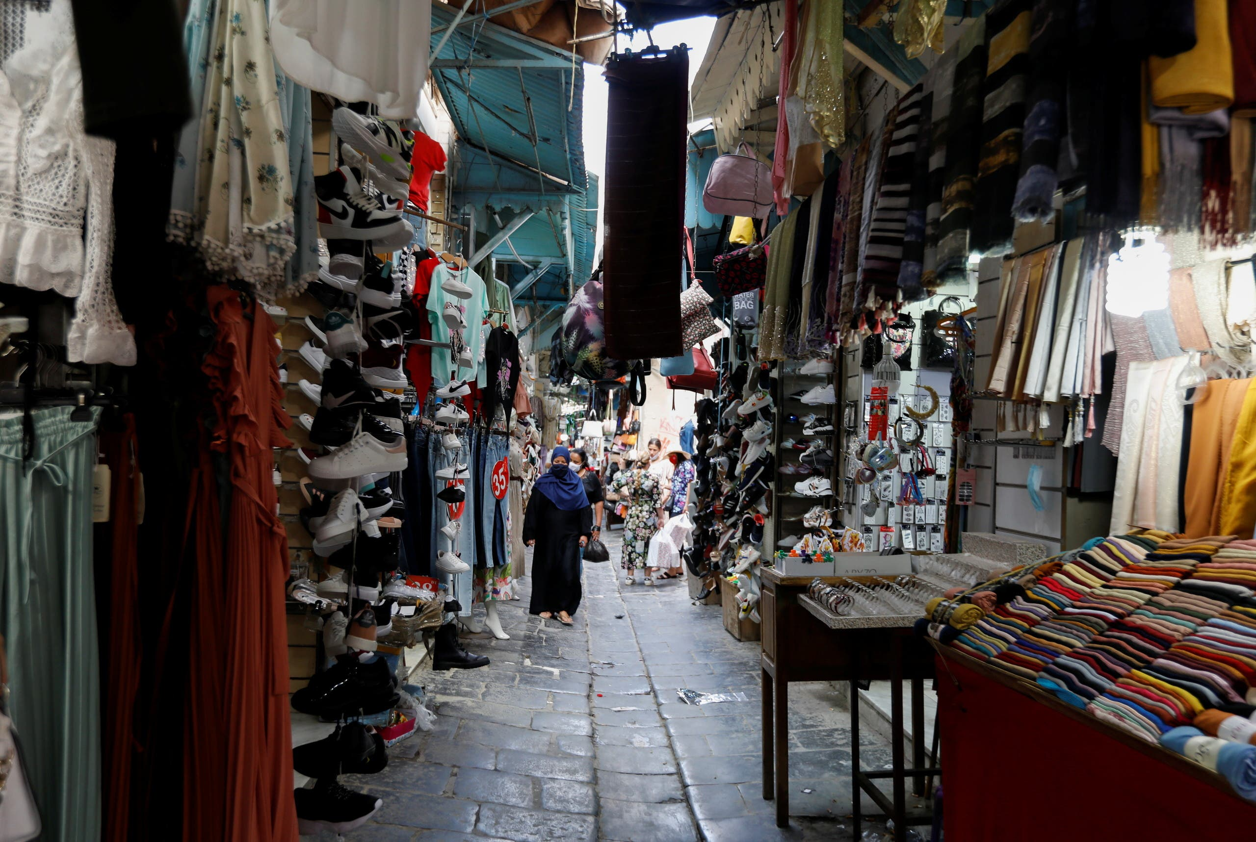 People walk past shops in the Medina, in the old city of Tunis, Tunisia, July 27, 2021. (Reuters)