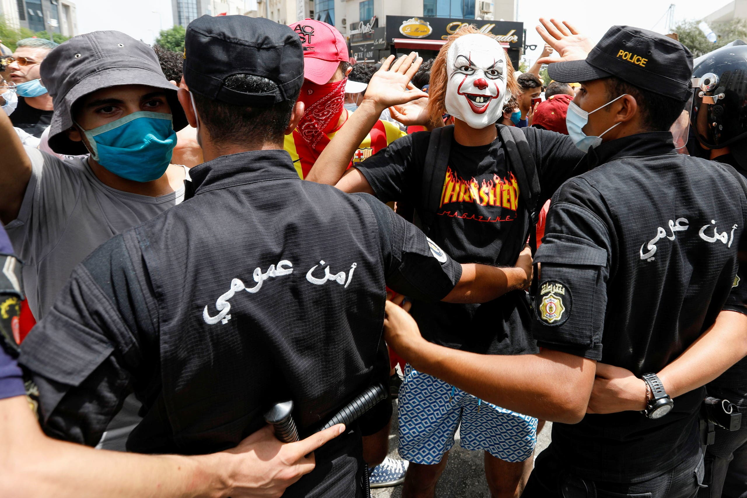 A demonstrator wearing a mask gestures in front of police officers standing guard during an anti-government protest in Tunis, Tunisia, July 25, 2021. (Reuters)