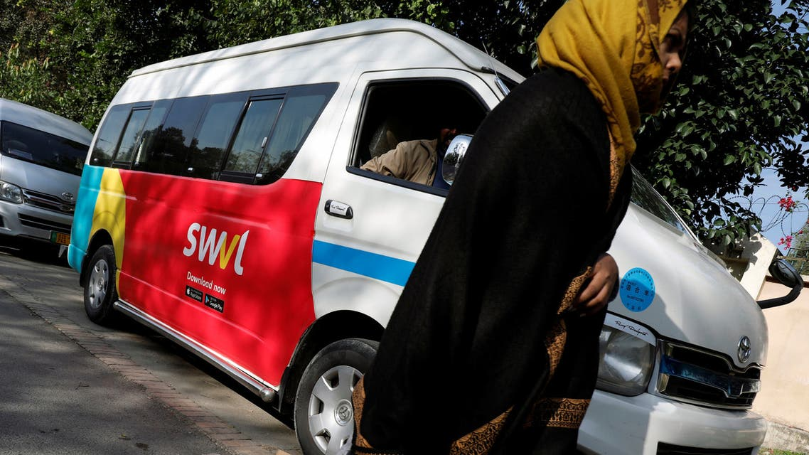 A woman walks past a vehicle with a logo of the Egyptian transport technology start-up Swvl, parked along a road in Islamabad, Pakistan, November 11, 2019. (Reuters)