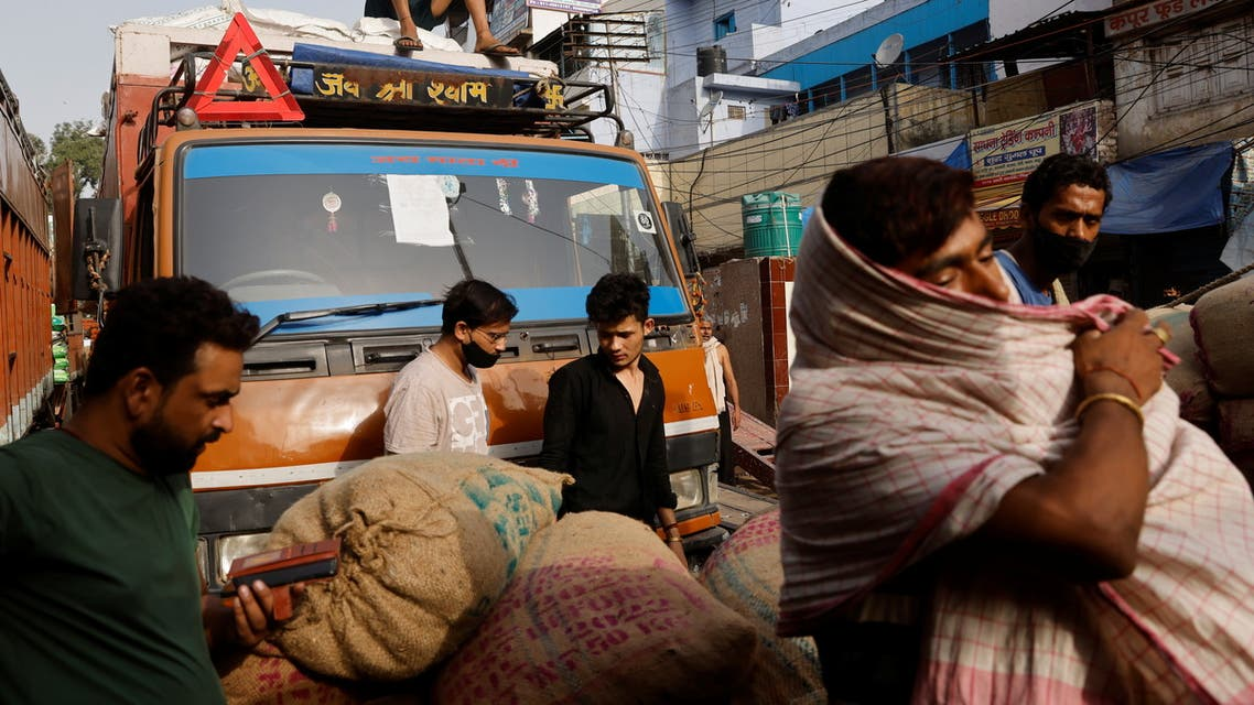 Workers load sacks of spices onto a truck at a wholesale market after authorities eased lockdown restrictions that were imposed to slow the spread of the coronavirus disease (COVID-19), in the old quarters of Delhi, India, June 8, 2021. (Reuters)