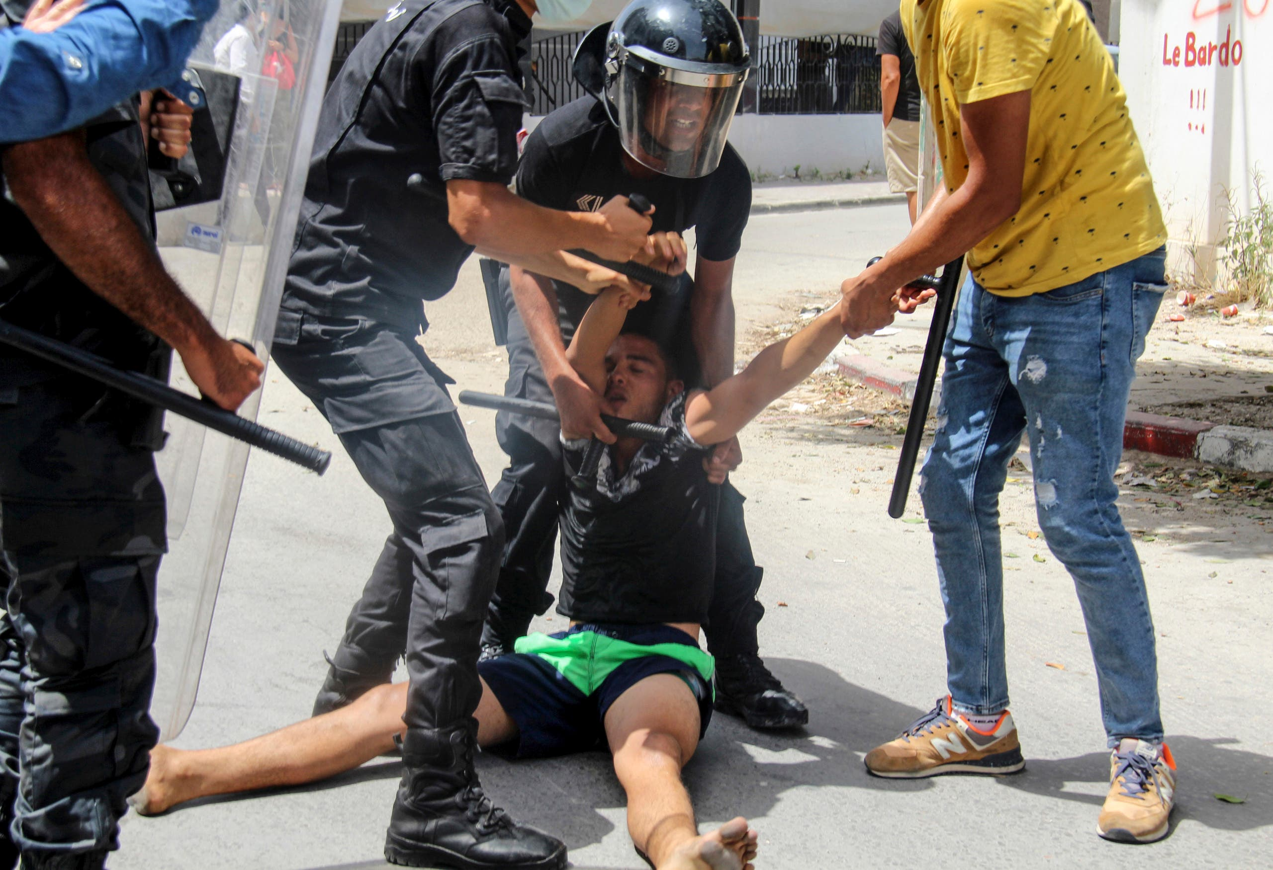 Tunisian police officers detain a protester during a demonstration in Tunis, Tunisia, Sunday, July 25, 2021. (AP)